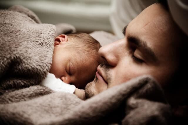 寝ている赤ちゃんとパパ